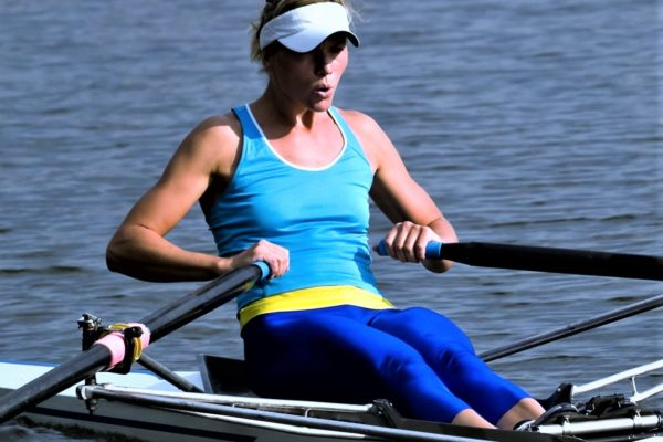 Sporty young lady rowing in boat on water